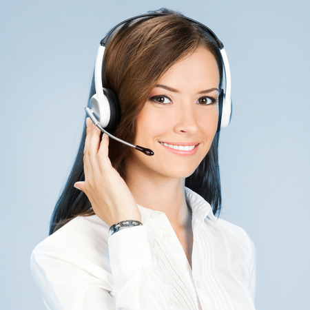 business woman phone: Portrait of happy smiling cheerful customer support phone operator in headset, over blue background