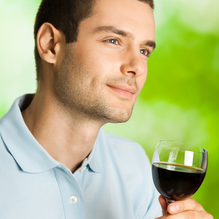 redwine: Portrait of attractive young man with glass of redwine, outdoor