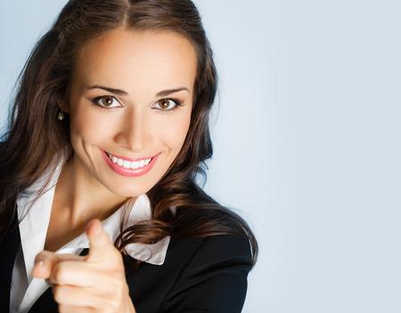 Retrato de mujer de negocios joven sonriente que señala el dedo en el espectador, sobre fondo azul