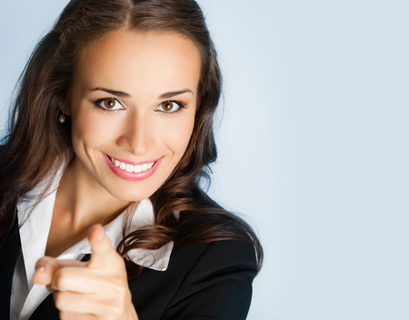 te negro: Retrato de mujer de negocios joven sonriente que se�ala el dedo en el espectador, sobre fondo azul