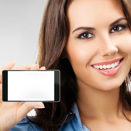 advertising space: Portrait of smiling young businesswoman showing no-name blank cellphone with copyspace, against grey background