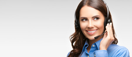 telephone headset: Portrait of smiling cheerful customer support phone operator in headset, with blank area for slogan, copyspace or product, against grey background