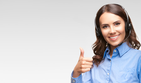 thumbs up woman: Portrait of smiling cheerful customer support phone operator in headset showing thumb up gesture, with blank area for copyspace or product, against grey background Stock Photo