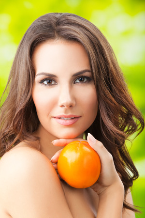 only one girl: Young woman with persimmon fruit, outdoors