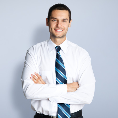 Portrait of happy smiling young businessman with crossed arms pose, against grey background