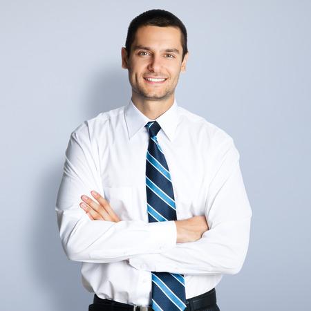 Portret van gelukkig lachende jonge zakenman met gekruiste armen opleveren, tegen een grijze achtergrond Stockfoto