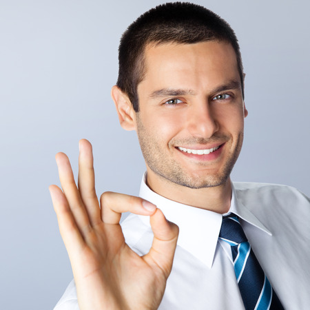 Happy smiling young businessman with okay gesture, against grey background photo