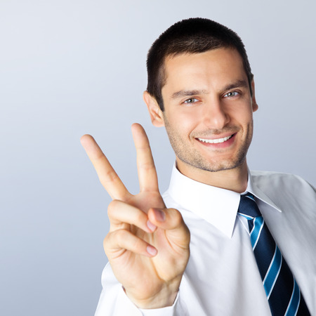 2 persons only: Happy smiling businessman showing two fingers, or victory gesture, against grey background