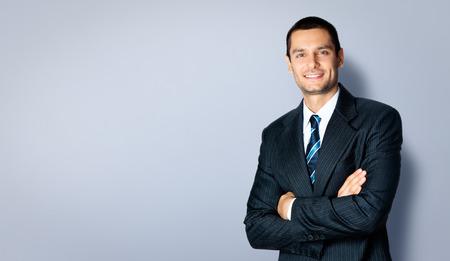 Lyckligt leende affärsman med korsade armar pose, med tom copyspace område för text eller slogan, mot grå bakgrund