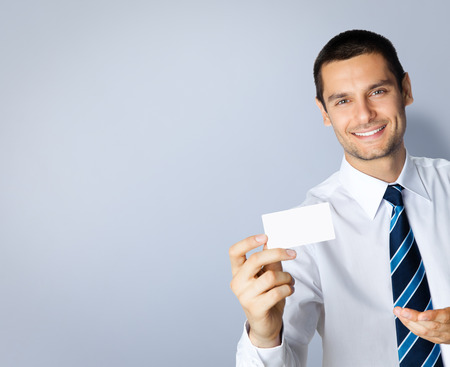 debet: Portrait of smiling businessman showing blank business or plastic credit card, with blank copyspace area for text or slogan, against grey background Stock Photo