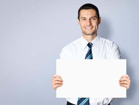 Portrait of happy smiling young businessman showing blank signboard, with copyspace area for text or slogan, against grey background