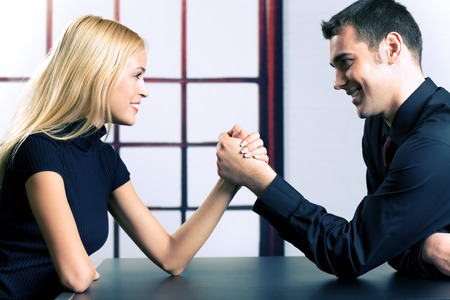 office force: Young happy couple or business people fighting in arm-wrestling Stock Photo
