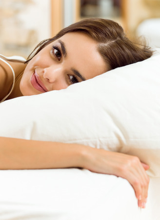 waking up: Young beautiful happy smiling woman waking up on bed