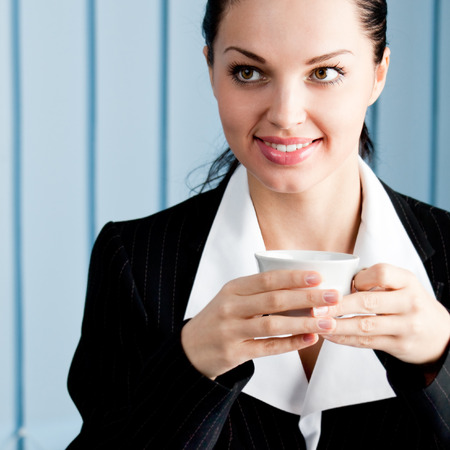 hot secretary: Young smiling businesswoman with coffee at office Stock Photo