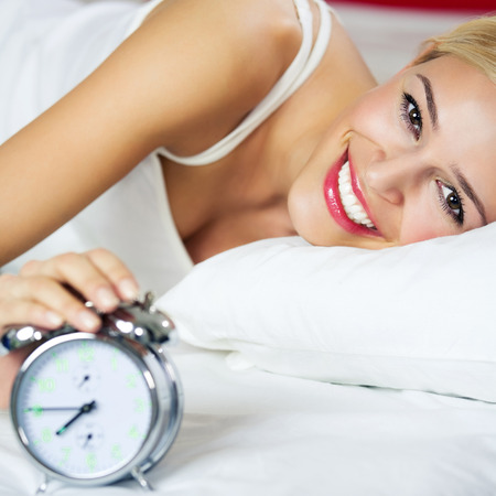 lazyness: Cheerful smiling woman waking up at bedroom Stock Photo