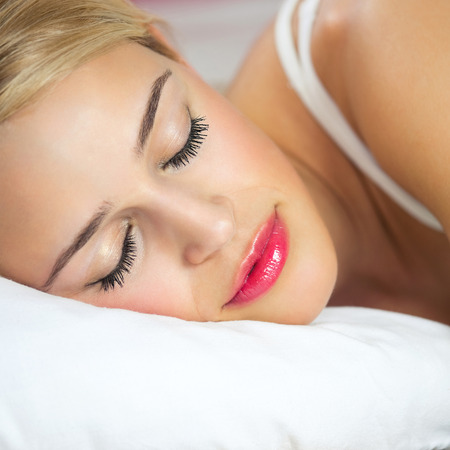 lazyness: Beautiful young sleeping woman at bedroom Stock Photo