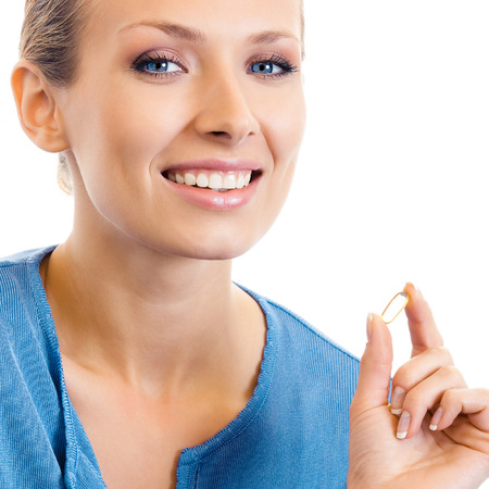 omega 3: Portrait of young woman with Omega 3 fish oil capsule, isolated over white background