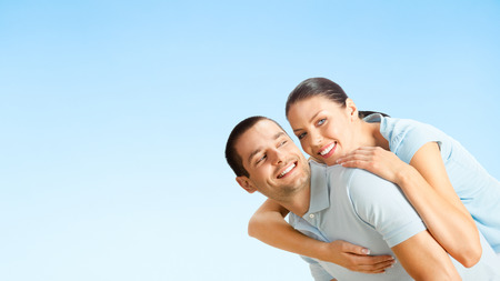 Cheerful young smiling amorous attractive couple, against blue sky background, with copyspace photo