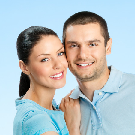 Cheerful young smiling amorous attractive couple, against blue sky background photo