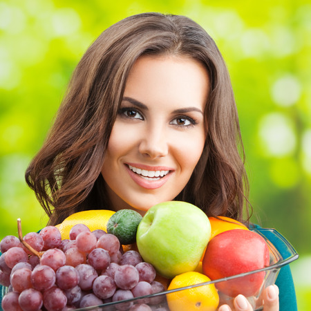 Cheerful smiling young woman with plate of fruits, outdoors photo