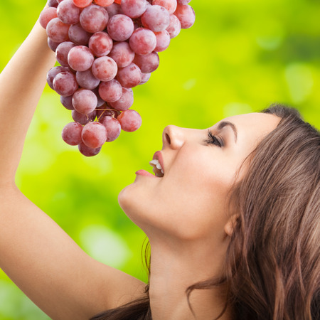 Cheerful smiling woman with grapes, outdoor photo