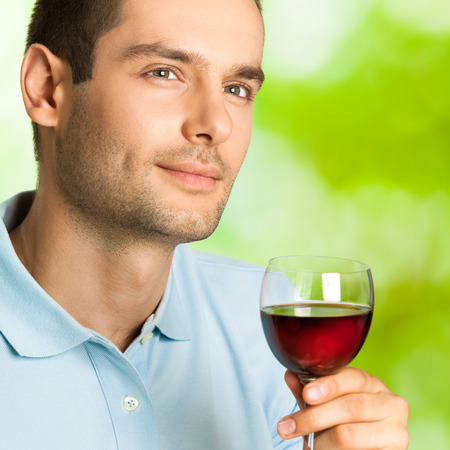 redwine: Portrait of handsome man with glass of redwine, outdoor Stock Photo