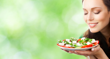 Young beautiful smiling woman with plate of salad, outdoor, with copyspace area for slogan or text 스톡 콘텐츠
