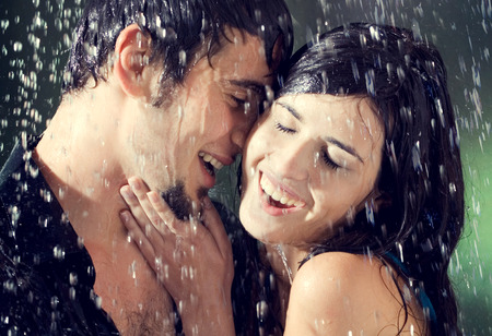 Young amorous couple hugging and kissing under a rain, outdoors photo