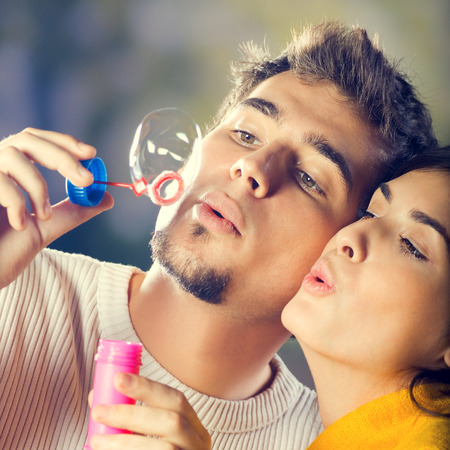 couple having fun: Portrait of young happy couple blowing bubbles, outdoor Stock Photo