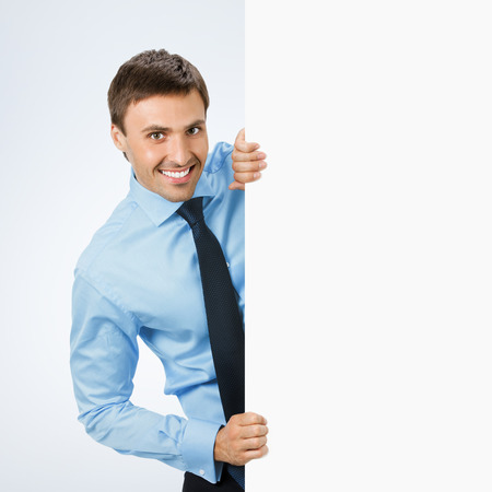 blank area: Happy smiling young business man showing blank signboard, over grey background, with copyspace area for text or slogan