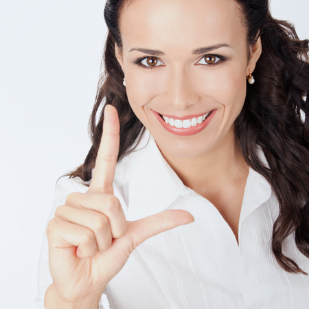 Happy smiling young business woman showing two fingers, against grey background photo