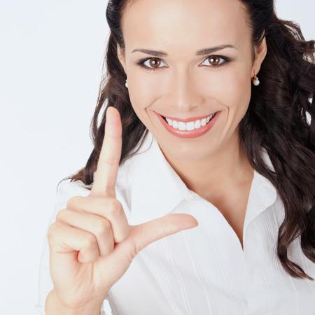 show bill: Mujer de negocios joven que muestra dos dedos, contra el fondo gris Feliz sonriente