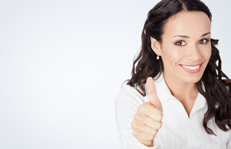 Happy smiling business woman showing thumbs up gesture, against grey background, with copyspace photo