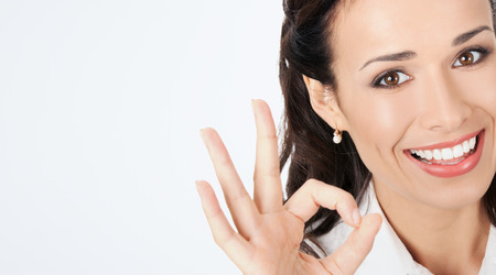 face work: Happy smiling young business woman showing okay gesture, against grey background, with copyspace Stock Photo