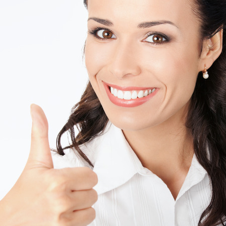 2 persons only: Happy smiling business woman showing thumbs up gesture, against grey background