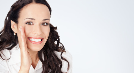 Portrait of happy smiling young business woman covering with hand her mouth, against grey background, with copyspace photo