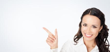 幸せな笑顔若いビジネス女性表示記号または copyspase copyspace で、灰色の背景の空白の領域 写真素材