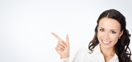Happy smiling young business woman showing blank area for sign or copyspase, against grey background, with copyspace Stock Photo