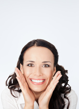 Portrait of young happy smiling surprised business woman, against grey background, with copyspace photo