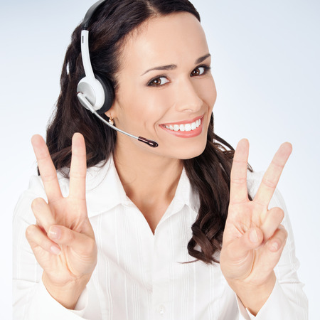 handsfree phone: Portrait of happy smiling cheerful customer support phone operator in headset showing two fingers, against grey background