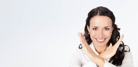 Happy smiling young business woman showing stop gesture, against grey background, with copyspace photo