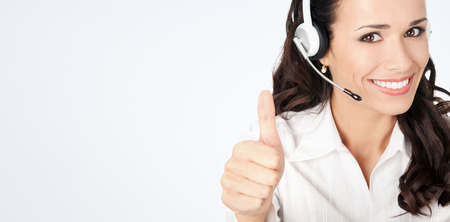 blank center: Portrait of happy smiling cheerful customer support phone operator in headset showing thumbs up gesture, against grey background, with copyspace