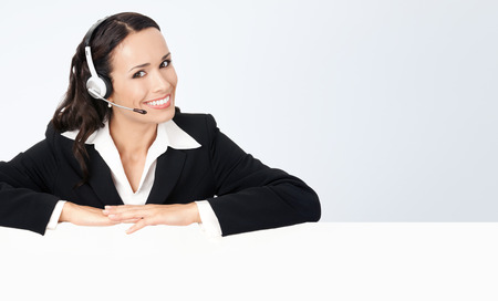 handsfree phone: Happy smiling young customer support phone operator in headset showing blank signboard, against grey background, with copyspace Stock Photo