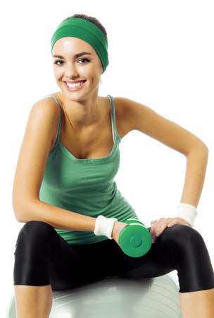 physical training: Happy smiling young woman in green fitness wear exercising with dumbbell and fitball, isolated against white background
