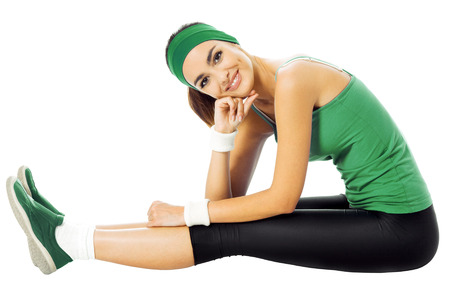 Happy smiling young woman in green fitness wear, isolated against white background photo