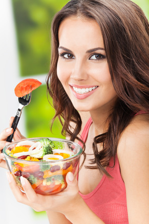 summer diet: Portrait of happy smiling young woman with vegetarian vegetable salad, outdoors