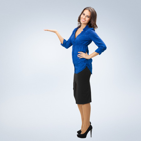 space for copy: Full body portrait of happy smiling young businesswoman showing something or copyspase for product or sign text