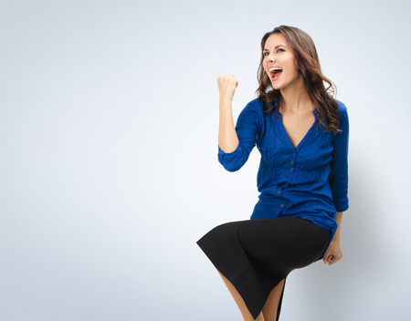 employe: Happy gesturing young cheerful smiling businesswoman, with copyspace area Stock Photo