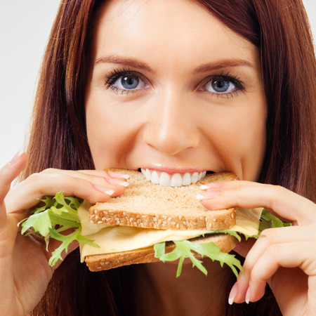 gluttonous: Happy young woman eating sandwich with cheese Stock Photo