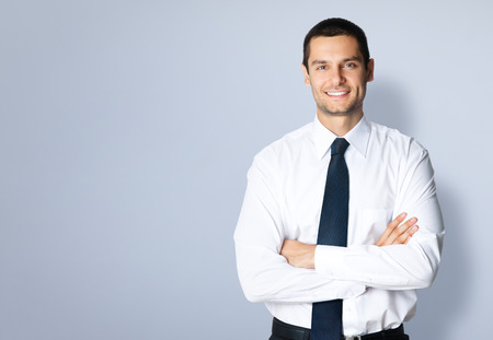 Portrait of cheerful young businessman with crossed arms pose, with blank copyspace area for text or slogan, against grey background photo